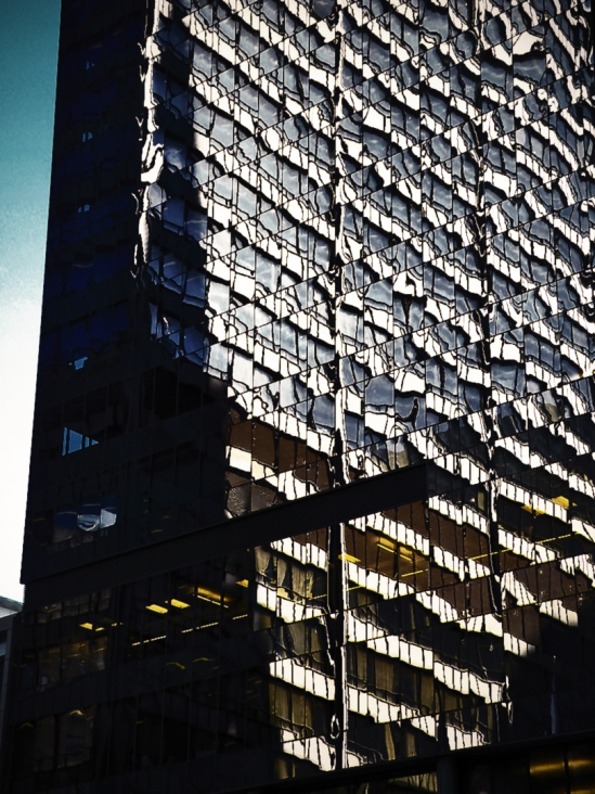 The Richard J. Daley Center, reflected in the tinted glass windows of the CBS television headquarters and studios